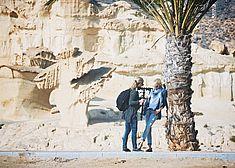 TREDY-fashion Online Magazin. Making-of Shooting in Alicante Spanien. Model lehnt an einer Palme