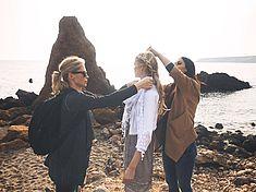 TREDY-fashion Online Magazin. Making-of Shooting in Alicante Spanien. Model steht an der Küste. Die Visagistin macht sie zurecht.